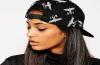 Une jeune femme porte une casquette noire