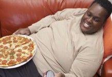 un homme obèse mange une pizza